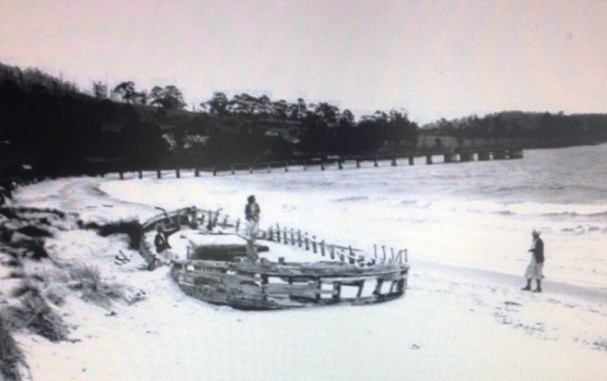Old black and white photo of the Annie Taylor shipwreck on Rheban Beach showing how she has shifted parallel to the shore, pointing northwest.