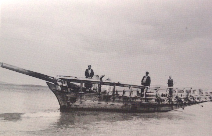 Old black and white photo of men standing on the Annie Taylor shipwreck on Rheban Beach in 1954.