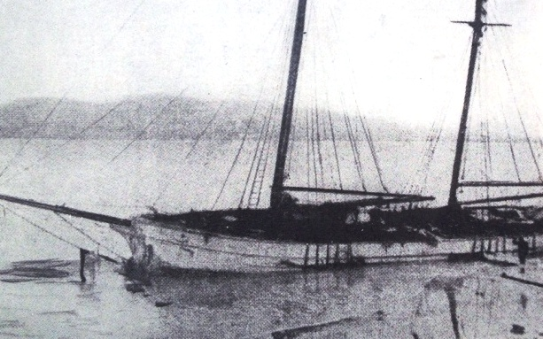 Black and white photo of the Annie Taylor at Rheban Beach not long after beaching, with water and flotsam around her.